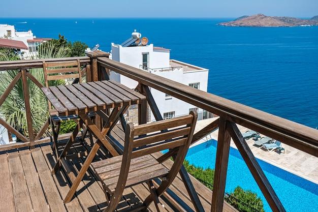 Houten terras van vakantievilla of hotel met twee stoeltafels met uitzicht op zee en zwembad.