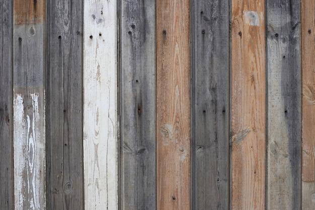 Houten textuurachtergrond. houten hek gemaakt van bruin grijs en wit geschilderde planken