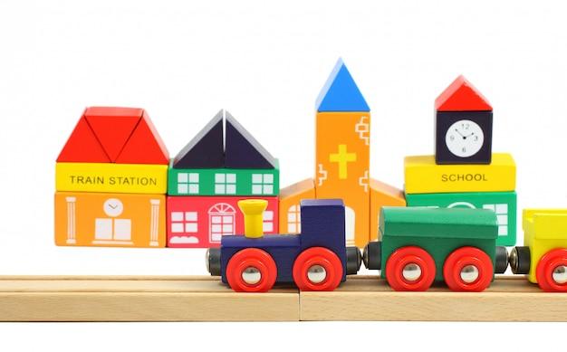 Houten trein op de spoorweg en huizen die van stuk speelgoed blokken worden gemaakt die over wit worden geïsoleerd