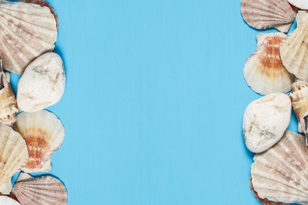 Houten turkooise achtergrond met frame gemaakt van zeeschelpen, bovenaanzicht