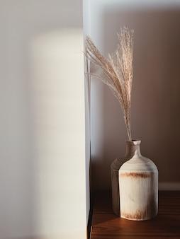 Houten vaas met pampagras tegen witte muur