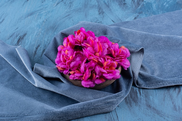 Houten vaas van verse paarse bloemen op blauw.