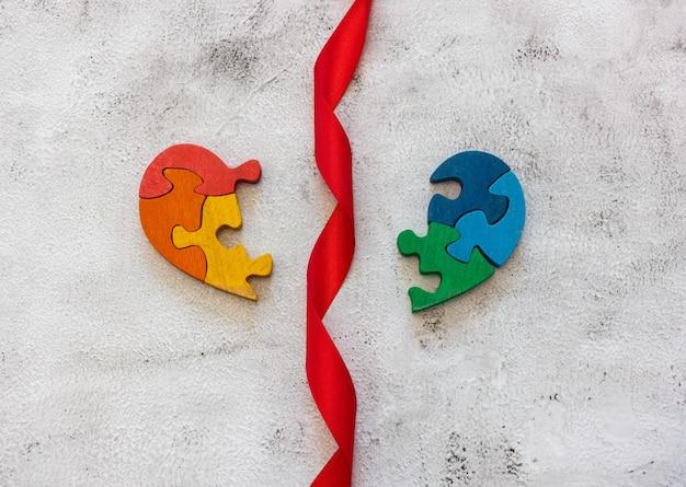 Houten veelkleurige puzzel in de vorm van een gebroken hart op een grijze achtergrond. rode plakband. concept valentijnsdag, relatie. ruimte voor tekst