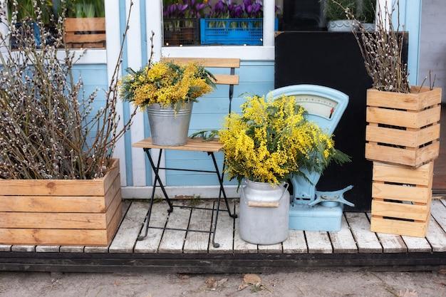 Houten veranda van huis met planten en takken gele mimosa
