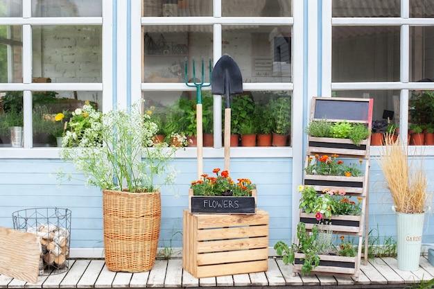 Houten veranda van huis met planten tuingereedschap en bloemen in doos zomerdecor veranda huis