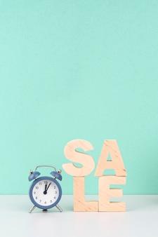 Houten verkoop belettering naast klok op blauwe achtergrond
