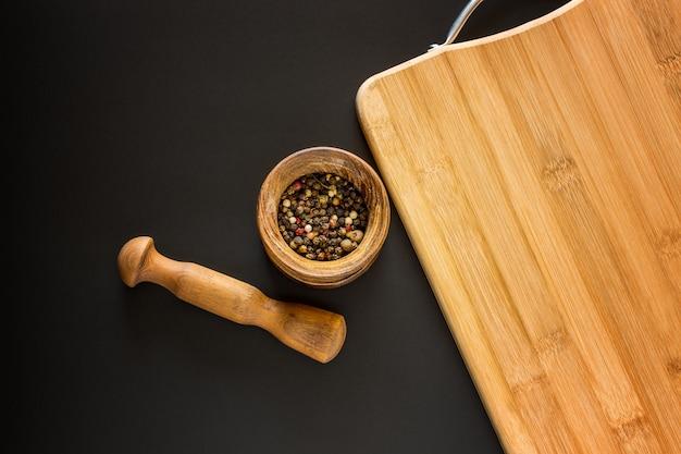 Houten vijzel met diverse kruiden en lege snijplank