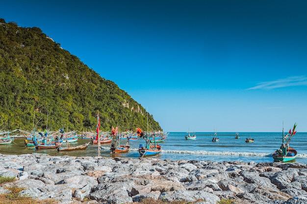Houten vissersboot op de andaman zee in thailand. oude houten vissersboten die de longtailboot tegenkwam aan de oostkust van de bergachtergrond van thailand