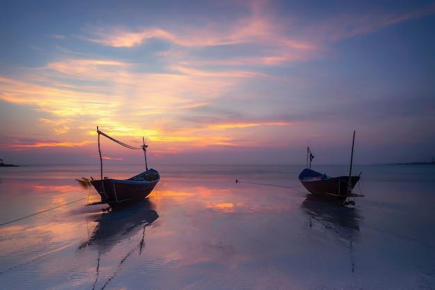 Houten vissersboot op overzees strand bij zonsondergang.