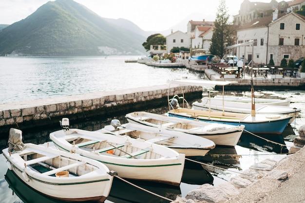 Houten vissersboten aangemeerd aan de kust tegen de achtergrond van bergen en huizen in perast