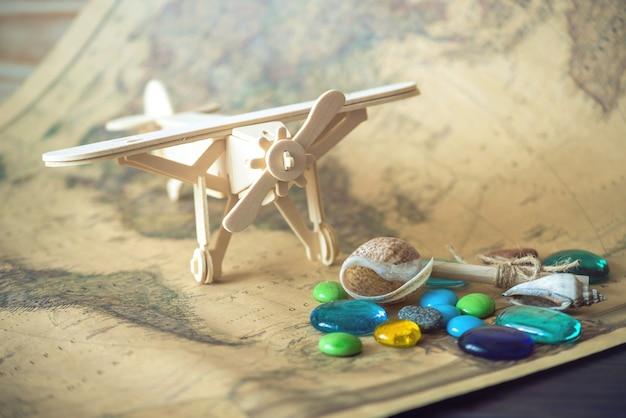 Houten vliegtuig speelgoed op een wereldkaart met gekleurde stenen en schelpen uit de zee in een retro stijl.