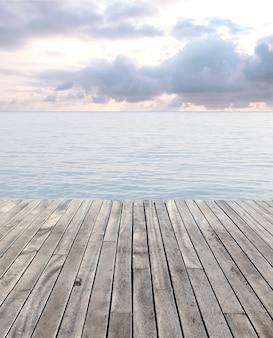 Houten vloer en blauwe zee met golven en bewolkte hemel