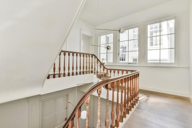 Houten vloer en klassieke balustrades van trappenhuis in luxe herenhuis met witte muren