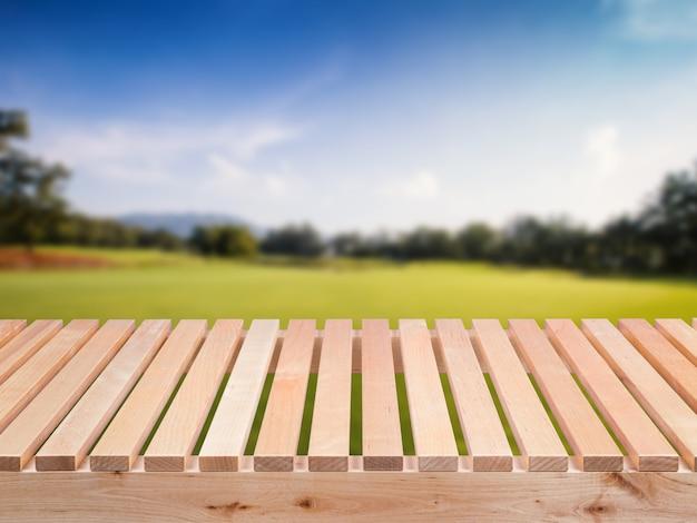 Houten vloer met groen veld en blauwe hemelachtergrond