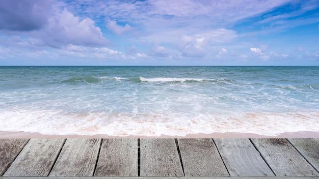Houten vloer op mooi tropisch zandig strand met blauwe oceaan en blauwe hemelachtergrond