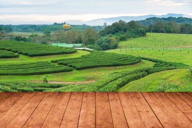 Houten vloer perspectief weergave met thee plantage boerderij en uitzicht op de bergen en hete luchtballon op achtergrond.