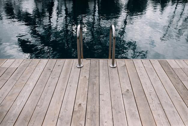 Houten vloer voor het zwembad. leuningen voor afdaling in het zwembad in het midden. buitenzwembad