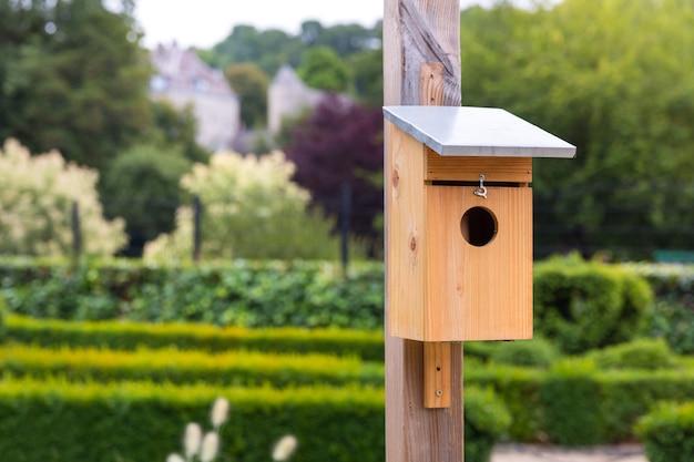 Houten vogelhuisje in groen park op zomerdag, europa. nestkast voor vogels, nesthuis close-up