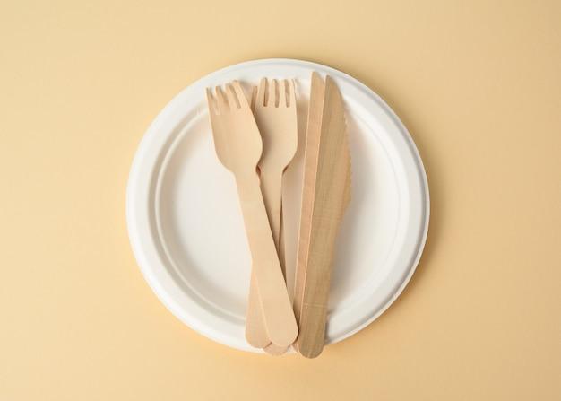 Houten vork en lege witte ronde bruine wegwerp bord gemaakt van gerecyclede materialen op een bruine achtergrond, bovenaanzicht. concept van de afwezigheid van niet-recyclebaar afval, afwijzing van plastic, bovenaanzicht