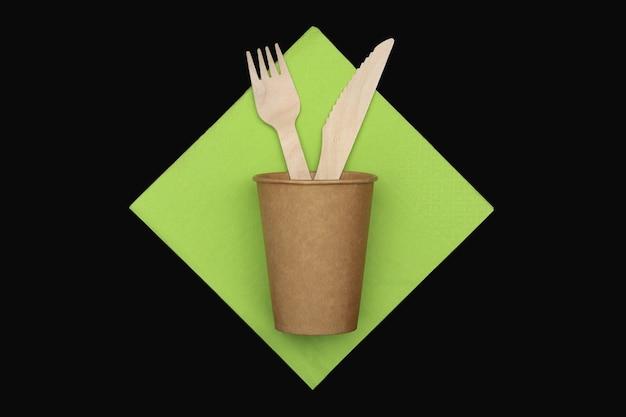 Houten vork en mes in papieren beker op groen servet op zwarte achtergrond, bovenaanzicht.