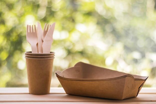 Houten vorken en messen in ambachtelijke bekers, papieren borden. milieuvriendelijk keukengerei voor eenmalig gebruik. ecologie, afvalvrij concept. milieubescherming.