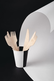 Houten vorken en messen in papieren beker op zwart-witte achtergrond. milieuvriendelijk wegwerpservies van natuurlijk materiaal. ecologisch begrip.