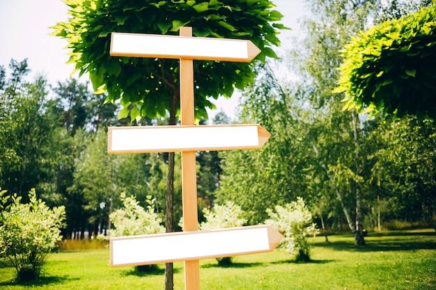 Houten wegwijzer in het park. eten en drinken. feest in het park. houten pijl. aanwijzer met plaats voor tekst.