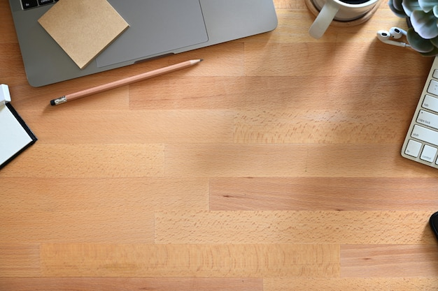 Houten werktafel met laptop, koffie en kopie ruimte.