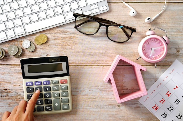 Houten werktafel met laptop toetsenbord rekenmachine klok huis model en benodigdheden thuis kosten concept.