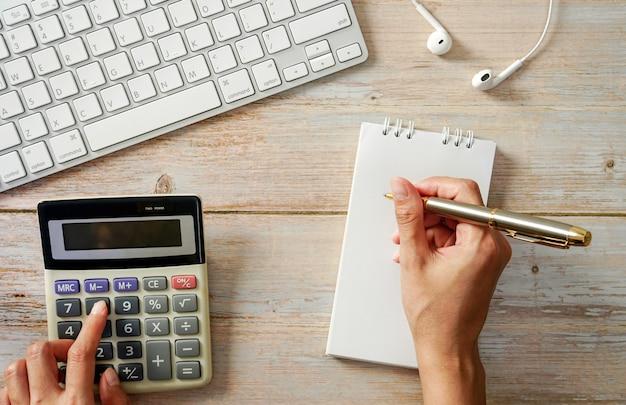 Houten werktafel notebook computer toetsenbord rekenmachine schetsboek een creatief bureau van bovenaf