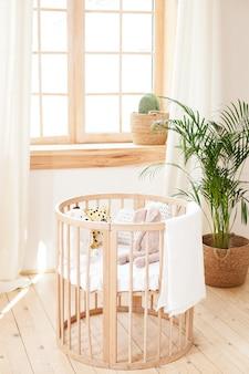 Houten wieg in een milieuvriendelijk gezellig interieur. lichtbruine kinderenslaapkamer met een houten lege wieg. gezellig huis hygge style design. kinderkamer in de scandinavische stijl. rustiek interieur