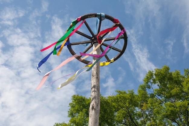 Houten wiel met kleurrijke linten op blauwe hemelachtergrond. slavische viering.