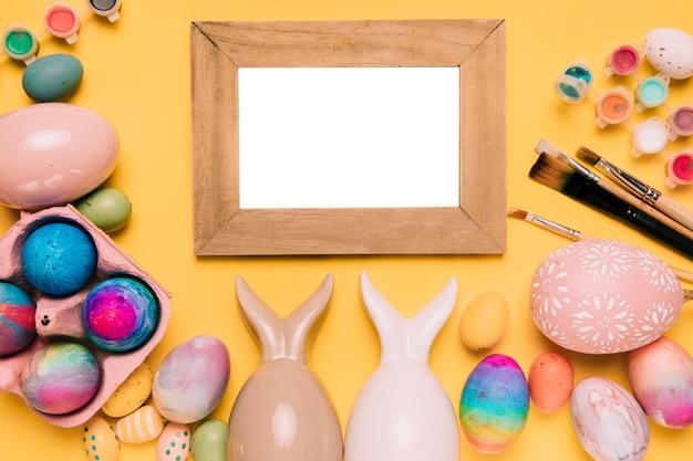 Houten wit frame met kleurrijke paaseieren op gele achtergrond