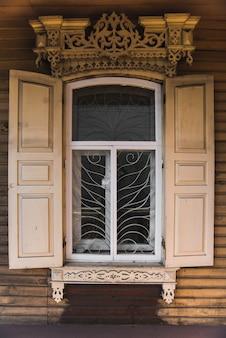 Houten wit raam met luiken en gebeeldhouwde patronen op de ramen in een rustiek oud huis