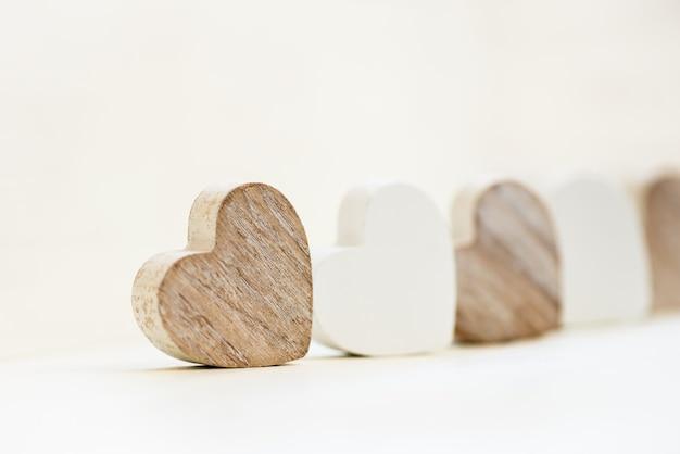 Houten witte en grijze harten in de houten witte lade