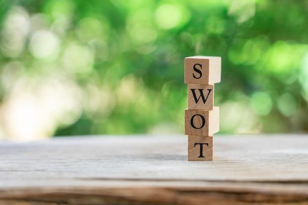 Houten woord swot geplaatst op het houten concept van de lijststrategie en bedrijfsconcept
