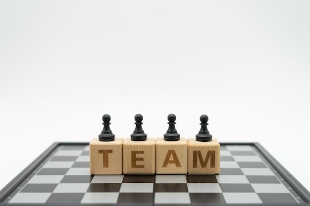 Houten woord team op een schaakbord met een schaakstuk op de rug onderhandelen
