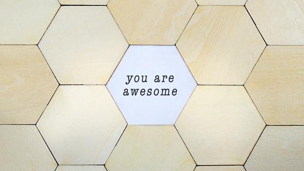 Houten zeshoek ontbreekt in puzzel, waardoor de woorden you are awesome zichtbaar worden in een conceptueel beeld van persoonlijke groei en optimisme