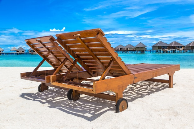 Houten zonnebank op tropisch strand in de malediven