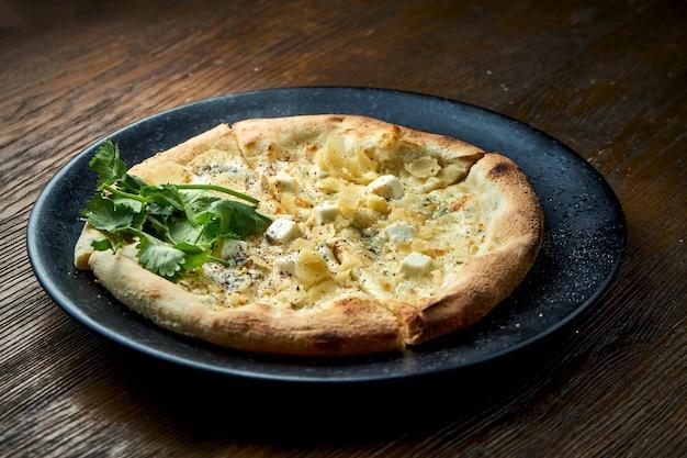 Houtgestookte pizza met 4 soorten kaas en witte saus op een houten achtergrond. pizzette een soort italiaanse pizza