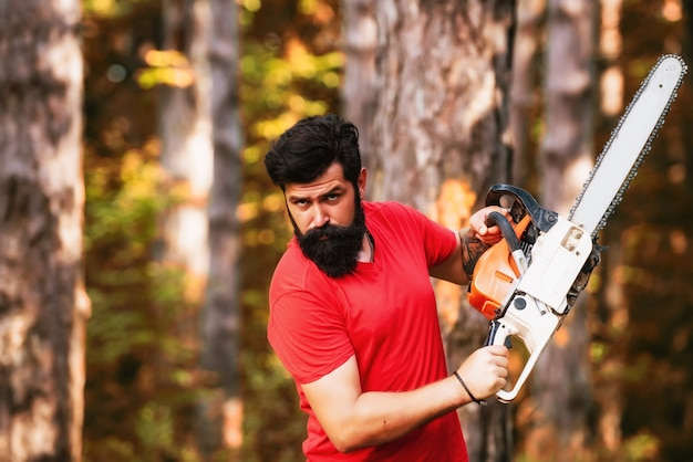 Houthakker met kettingzaag op zagerij. knappe houthakker dichtbij bos.