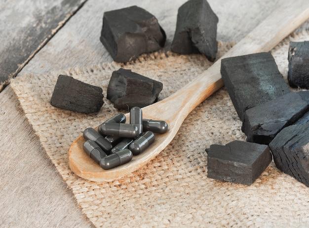 Houtskool en houtskoolcapsule op hennepzak met houten achtergrond. houtskoolcapsule om diarree te genezen en gifstoffen in de darm te absorberen.