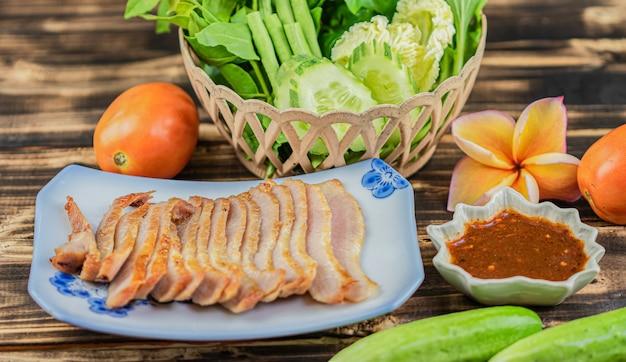 Houtskool-gekookte varkensvleeshals met vele groente op houten lijstachtergrond.