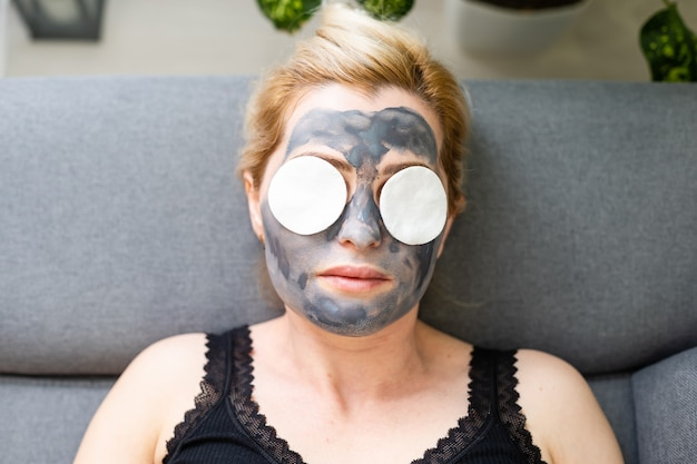 Houtskool gezichtsmasker of zwarte klei modder. mooie vrouw met zwart masker op haar gezicht, close-up studio hoofdschot. natuurlijk cosmetisch concept.