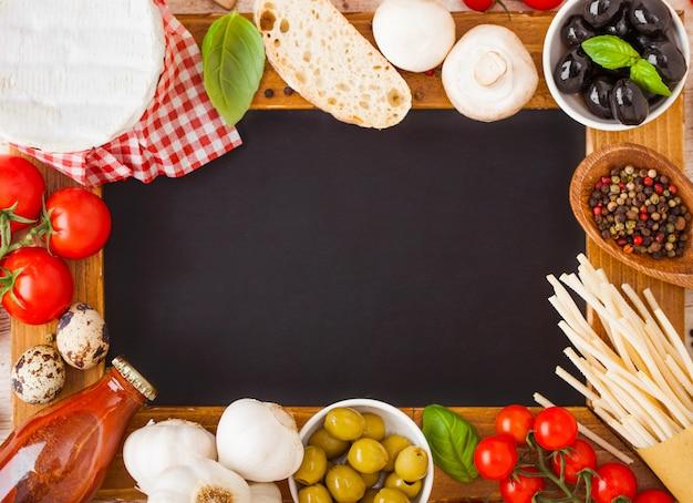 Houtskool houten menubord met zelfgemaakte spaghettideegwaren met kwarteleitjes en kaas. klassiek italiaans dorpsvoedsel. knoflook, champignons, zwarte en groene olijven, houten spatel.