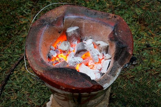 Houtskool in fornuis met brand op tuin in thailand