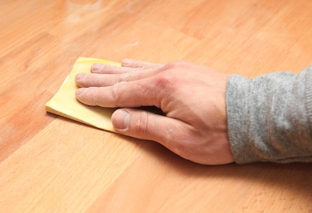 Houtslijpproces door schuurpapier. de jonge timmerman werkt met hout
