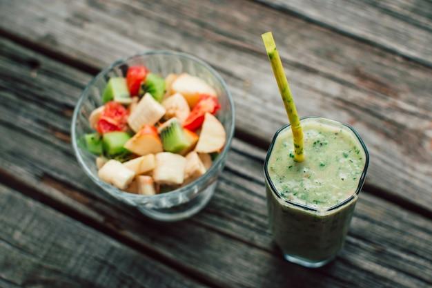 Houtstructuursalade in een glazen container met verschillende vruchten naast groene smoothie