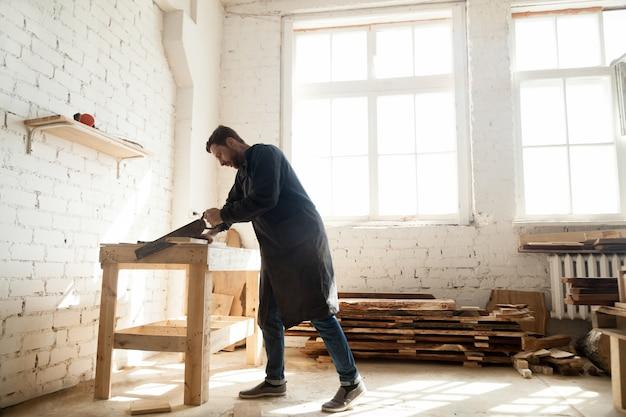 Houtwerk en constructie. timmerman met handzaag voor het hakken van houten plank