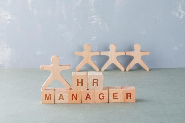 Hr manager concept met houten blokken met woorden erop, houten menselijke figuren.